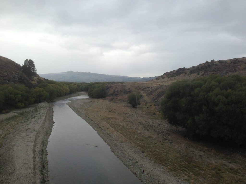 Otago Central Rail Trail view of a river and mountains in the distance