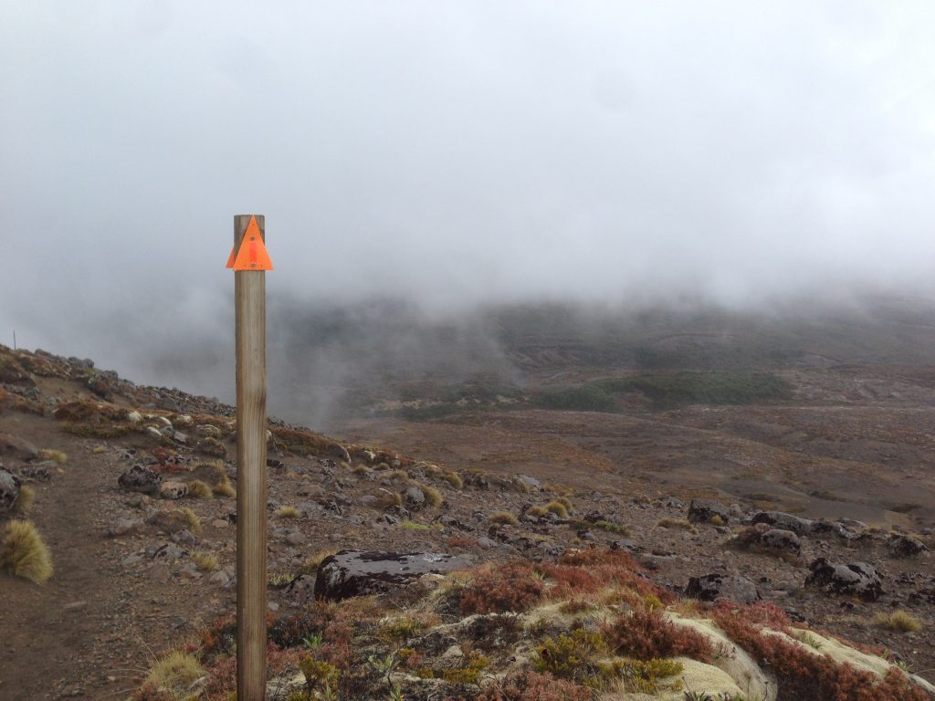 Trail marker against the fog on the Tongariro Northern Circuit